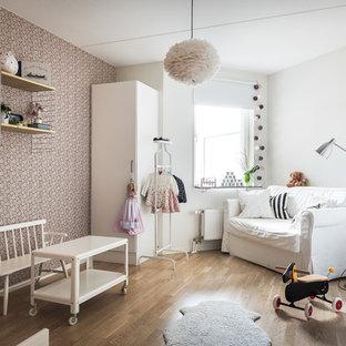 Inredning av ett nordiskt mellanstort barnrum kombinerat med sovrum, med lila väggar, mellanmörkt trägolv och brunt golv