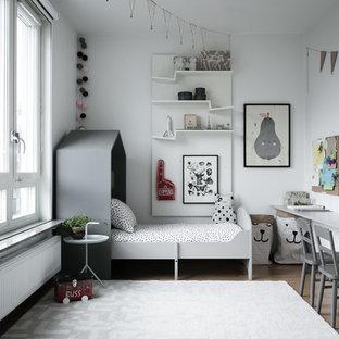 Bild på ett mellanstort nordiskt könsneutralt barnrum kombinerat med sovrum och för 4-10-åringar, med vita väggar, mellanmörkt trägolv och brunt golv