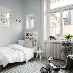 Inspiration för mellanstora nordiska pojkrum kombinerat med sovrum och för 4-10-åringar, med blå väggar, mellanmörkt trägolv och brunt golv