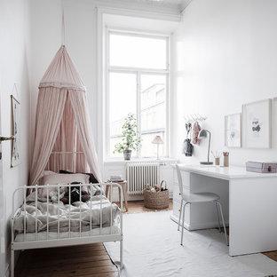 Nordisk inredning av ett mellanstort flickrum kombinerat med sovrum och för 4-10-åringar, med vita väggar, mellanmörkt trägolv och brunt golv