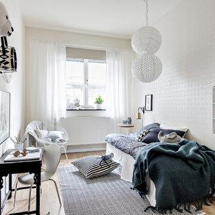 Idéer för att renovera ett mellanstort nordiskt könsneutralt barnrum kombinerat med sovrum, med vita väggar, ljust trägolv och brunt golv
