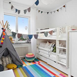 Bild på ett mellanstort skandinaviskt könsneutralt barnrum kombinerat med sovrum och för 4-10-åringar, med vita väggar