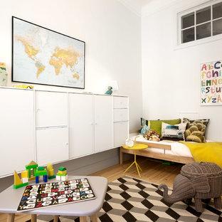 Idéer för ett modernt könsneutralt småbarnsrum kombinerat med lekrum, med vita väggar, mellanmörkt trägolv och beiget golv