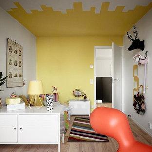 Idéer för att renovera ett mellanstort eklektiskt könsneutralt barnrum, med ljust trägolv och flerfärgade väggar