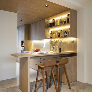 Photo of a contemporary breakfast bar in Singapore with light wood cabinets.