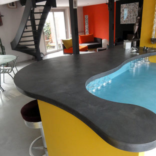 Seated home bar - large contemporary l-shaped concrete floor and gray floor seated home bar idea in Nantes with concrete countertops and blue backsplash