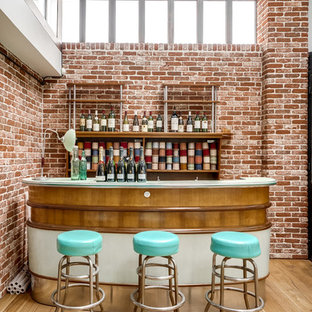Aménagement d'un grand bar de salon linéaire industriel avec des tabourets, un placard sans porte, un sol beige, des portes de placard en bois brun, un sol en bois clair et un plan de travail blanc.
