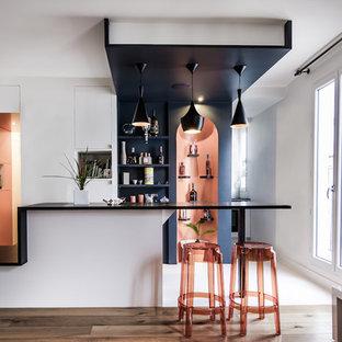 Idée de décoration pour un bar de salon linéaire design de taille moyenne avec un sol en bois brun, des tabourets et un placard sans porte.