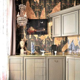Cette image montre un bar de salon bohème avec un évier encastré, un placard avec porte à panneau surélevé, des portes de placard grises, une crédence multicolore et un sol gris.