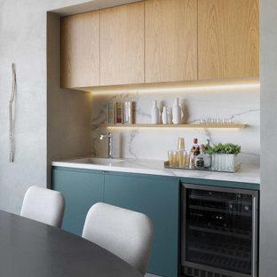 Idée de décoration pour un petit bar de salon avec évier linéaire design avec un évier intégré, un placard à porte plane, des portes de placard bleues, une crédence grise, un sol gris et un plan de travail gris.