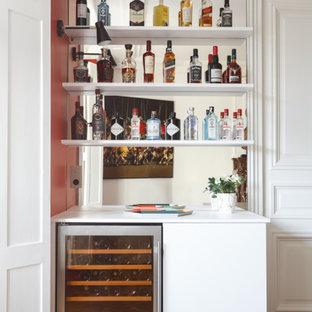 パリの小さいモダンスタイルのおしゃれなドライ バー (I型、シンクなし、フラットパネル扉のキャビネット、白いキャビネット、ラミネートカウンター、グレーのキッチンパネル、ミラータイルのキッチンパネル、無垢フローリング、茶色い床、白いキッチンカウンター) の写真