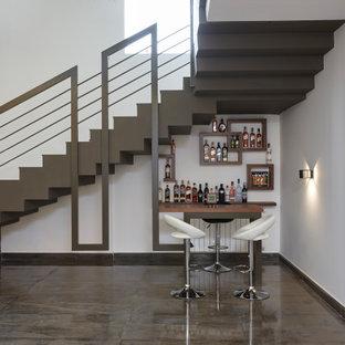 Ispirazione per un piccolo bancone bar contemporaneo con mensole sospese e pavimento grigio