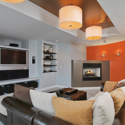 Inspiration for a contemporary underground carpeted and gray floor basement remodel in Philadelphia with a corner fireplace, orange walls and a metal fireplace
