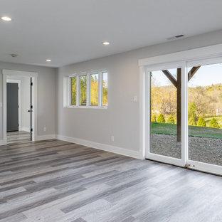 Aménagement d'un grand sous-sol classique donnant sur l'extérieur avec un bar de salon, un mur gris, un sol en vinyl et un sol gris.