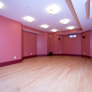 Cette photo montre un grand sous-sol chic enterré avec un mur rose et un sol en bois clair.
