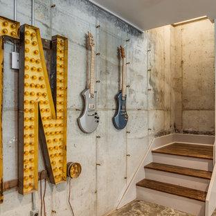 Idées déco pour un sous-sol contemporain enterré avec un mur gris et béton au sol.