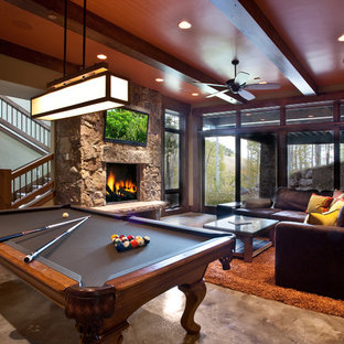 Basement - rustic walk-out concrete floor and gray floor basement idea in Salt Lake City with a standard fireplace, a stone fireplace and brown walls
