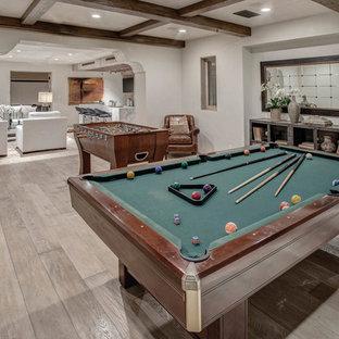 Cette photo montre un sous-sol méditerranéen avec salle de jeu, un mur blanc et un sol en bois brun.