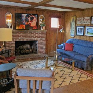 Cette image montre un sous-sol style shabby chic donnant sur l'extérieur et de taille moyenne avec un mur marron, un sol en bois brun, une cheminée standard, un manteau de cheminée en brique et un sol marron.