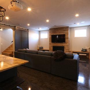 Aménagement d'un sous-sol moderne enterré et de taille moyenne avec un mur gris, une cheminée standard, un manteau de cheminée en carrelage et un sol bleu.