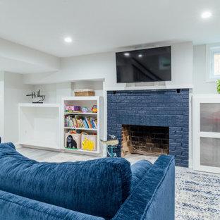 Aménagement d'un sous-sol classique semi-enterré et de taille moyenne avec un mur blanc, un sol en bois clair, une cheminée standard, un manteau de cheminée en brique et un sol gris.