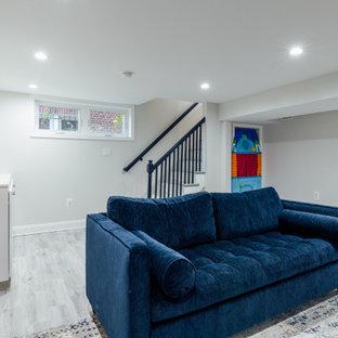 Cette photo montre un sous-sol chic semi-enterré et de taille moyenne avec un mur blanc, un sol en bois clair, une cheminée standard, un manteau de cheminée en brique et un sol gris.