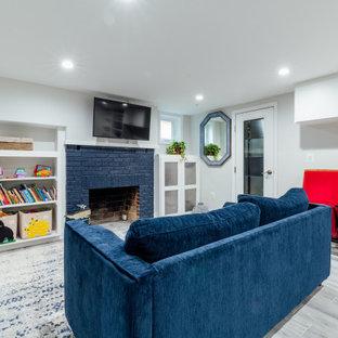 Idées déco pour un sous-sol classique semi-enterré et de taille moyenne avec un mur blanc, un sol en bois clair, une cheminée standard, un manteau de cheminée en brique et un sol gris.