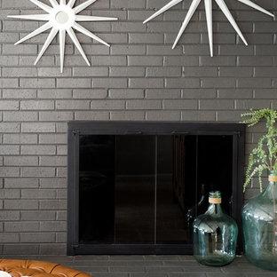 Réalisation d'un grand sous-sol minimaliste semi-enterré avec un mur gris, moquette, un poêle à bois, un manteau de cheminée en brique et un sol beige.