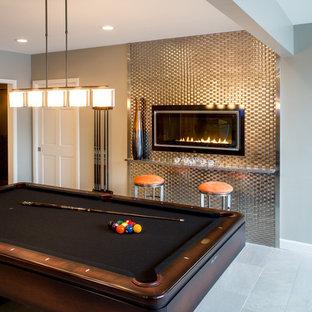 Aménagement d'un très grand sous-sol éclectique donnant sur l'extérieur avec un sol en carrelage de céramique, une cheminée ribbon, un manteau de cheminée en métal et un mur gris.