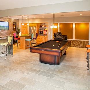 Cette image montre un très grand sous-sol bohème donnant sur l'extérieur avec un sol en carrelage de céramique et un mur orange.