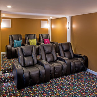 Huge eclectic walk-out carpeted basement photo in St Louis with orange walls