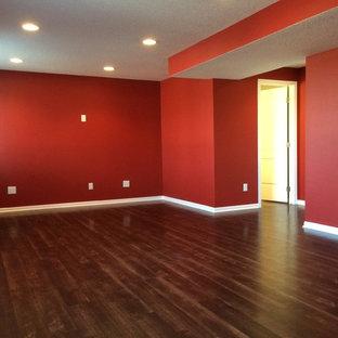 Aménagement d'un grand sous-sol classique semi-enterré avec un mur rouge, un sol en bois foncé et aucune cheminée.