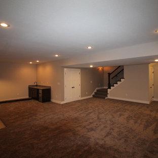 Exemple d'un grand sous-sol chic donnant sur l'extérieur avec un mur gris, moquette et un sol gris.