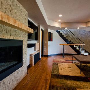 Réalisation d'un très grand sous-sol design donnant sur l'extérieur avec un sol en bambou, une cheminée standard et un manteau de cheminée en pierre.