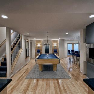 Exemple d'un grand sous-sol tendance donnant sur l'extérieur avec un mur blanc, un sol en bois clair, un manteau de cheminée en métal, une cheminée ribbon et un sol beige.