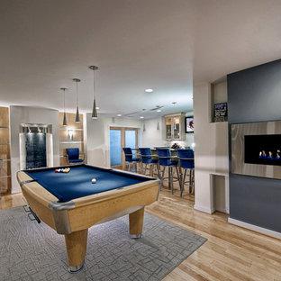 Cette image montre un grand sous-sol design donnant sur l'extérieur avec un mur bleu, un sol en bois clair, un manteau de cheminée en métal, une cheminée ribbon et un sol beige.