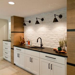 Foto di una grande taverna design con sbocco, pareti bianche, pavimento con piastrelle in ceramica, camino classico e pavimento beige
