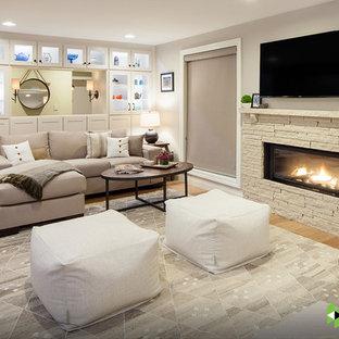 Réalisation d'un sous-sol tradition donnant sur l'extérieur avec un mur gris, une cheminée ribbon, un sol en bois clair et un sol beige.