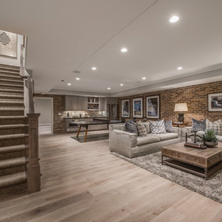 Cette image montre un grand sous-sol traditionnel avec un sol en bois clair, aucune cheminée et un sol marron.
