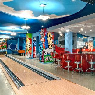 Idée de décoration pour un sous-sol design enterré avec un mur bleu, béton au sol, aucune cheminée et salle de jeu.