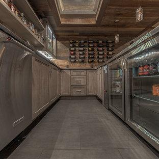 Idee per una grande taverna rustica interrata con pareti marroni, camino sospeso, cornice del camino piastrellata, pavimento in gres porcellanato e pavimento grigio