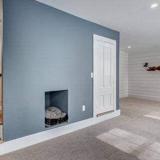 Exemple d'un grand sous-sol victorien donnant sur l'extérieur avec un mur bleu, moquette et aucune cheminée.