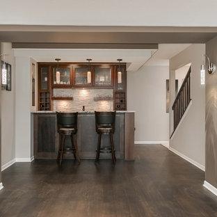 Exemple d'un grand sous-sol chic donnant sur l'extérieur avec un mur gris, un sol en bois foncé, une cheminée d'angle, un manteau de cheminée en carrelage et un sol marron.