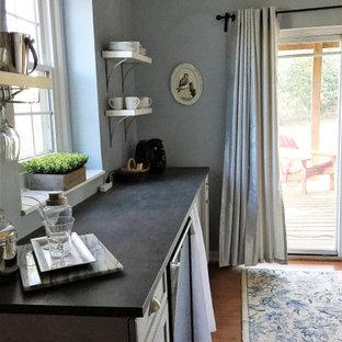 Idée de décoration pour un petit sous-sol style shabby chic donnant sur l'extérieur avec un mur bleu, un sol en vinyl et un sol marron.