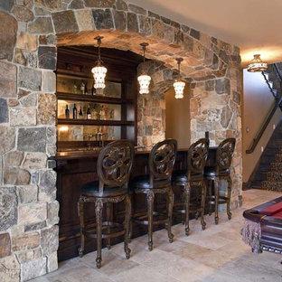 Idée de décoration pour un sous-sol tradition avec un mur beige, un sol en travertin, un sol beige et un bar de salon.