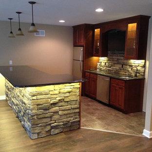 Réalisation d'un grand sous-sol design donnant sur l'extérieur avec un mur marron, sol en stratifié et un sol marron.