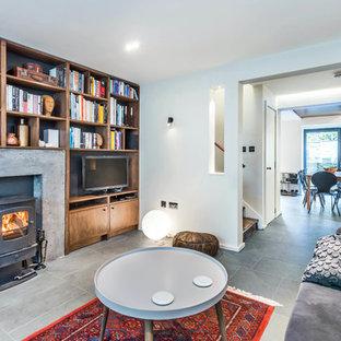 Idee per una taverna design con sbocco, pavimento in ardesia, stufa a legna, cornice del camino in cemento e pavimento grigio