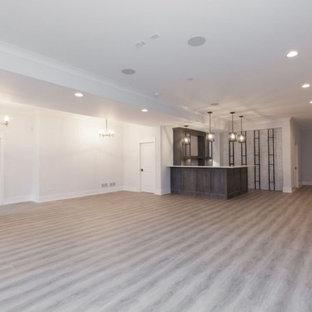 Aménagement d'un grand sous-sol campagne avec un bar de salon, un mur blanc, un sol en bois clair et un sol gris.