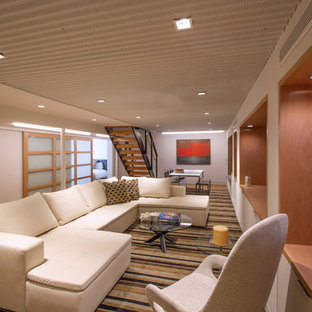 Idée de décoration pour un très grand sous-sol minimaliste donnant sur l'extérieur avec un mur blanc, moquette, aucune cheminée et un sol marron.