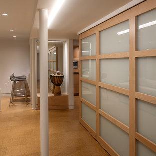 Idee per una taverna moderna seminterrata di medie dimensioni con pareti bianche, pavimento in sughero, nessun camino e pavimento beige